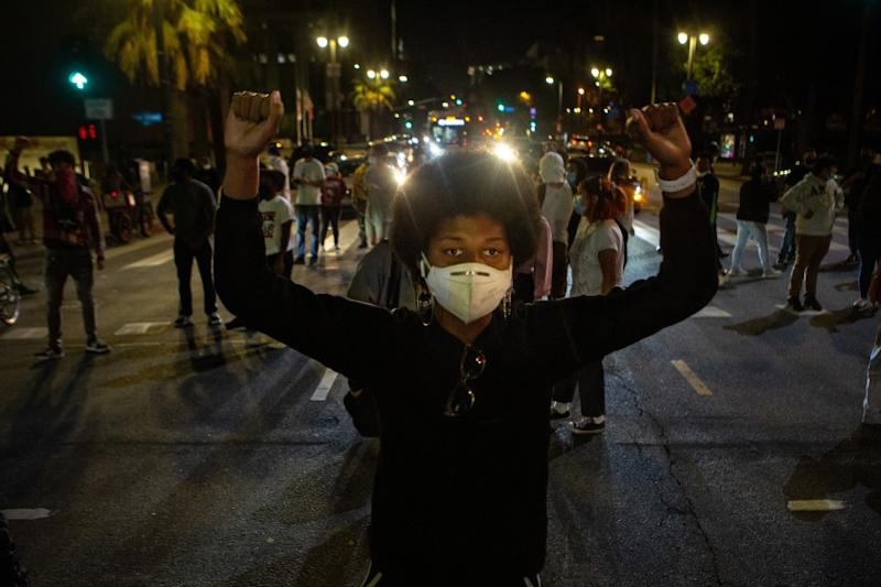 LOS ANGELES, CA - MAY 27: Keni James, 21, of Los Angeles holds both of her fist up in protest as she and other demonstrators block roads in DTLA while protesting the killing of George Floyd in Minnesota by police on Wednesday, May 27, 2020 in Los Angeles, CA. (Jason Armond / Los Angeles Times)
