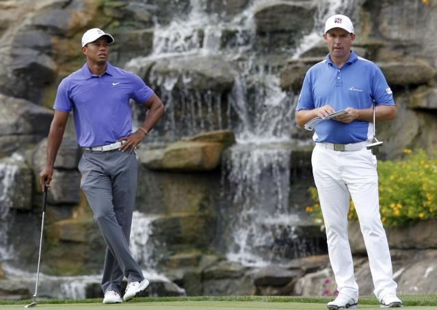 Tiger Woods (L) of the U.S. and Padraig Harrington of Ireland look on as they wait to putt on the 13th green during the first round of the PGA Championship at Valhalla Golf Club in Louisville, Kentucky, August 7, 2014. REUTERS/John Sommers II (UNITED STATES - Tags: SPORT GOLF)