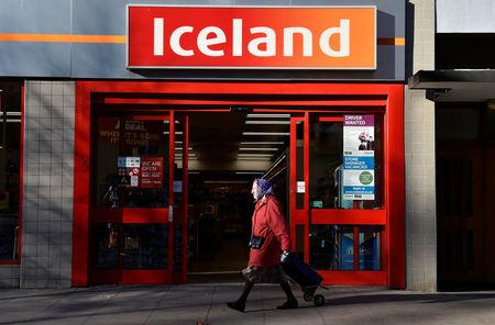 FILE PHOTO: A woman walks past an Iceland store in London