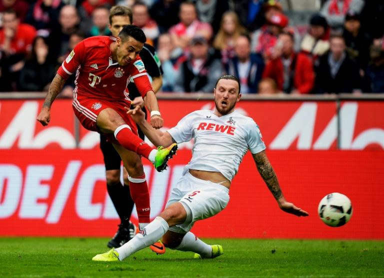 Cologne's midfielder Marco Hoeger and Bayern Munich's midfielder Thiago Alcantara vie for the ball during the German First division Bundesliga football match March 4, 2017
