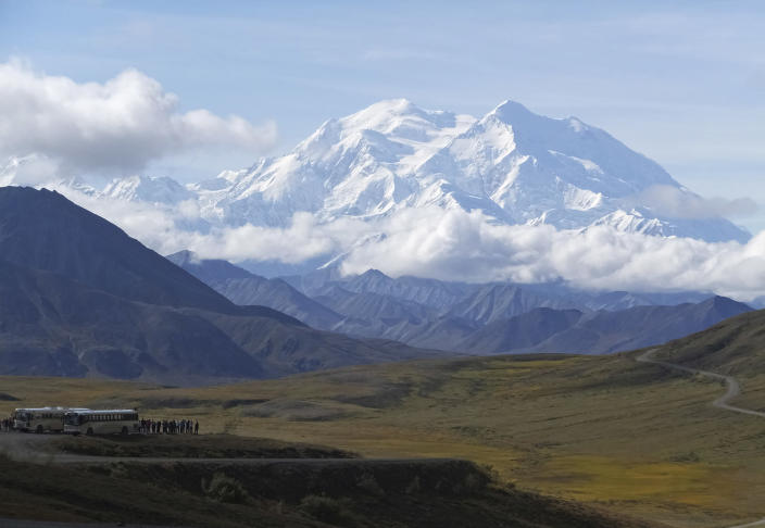 FILE - In this Aug. 26, 2016, file photo sightseeing buses and tourists are seen at a pullout popular for taking in views of North America's tallest peak, Denali, in Denali National Park and Preserve, Alaska. A climber was killed and another was significantly injured when they were hit by a falling block of glacier ice in Alaska's Denali National Park and Preserve, an official said Friday, May 14, 2021. The two were hit by the hanging serac after it dislodged from a peak off the West Fork of the Ruth Glacier. (AP Photo/Becky Bohrer, File)