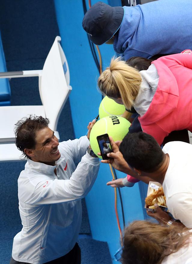 Rafael Nadal of Spain signs autographs for fans after defeating Kei Nishikori of Japan during their fourth round match at the Australian Open tennis championship in Melbourne, Australia, Monday, Jan. 20, 2014.(AP Photo/Eugene Hoshiko)