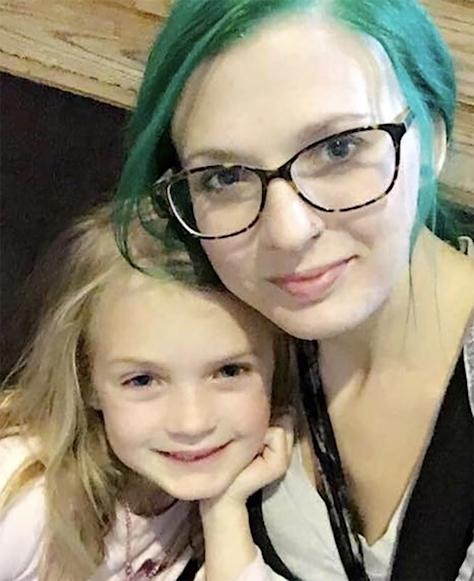 photo of woman with blue hair and glasses posing with daughter who has blonde hair