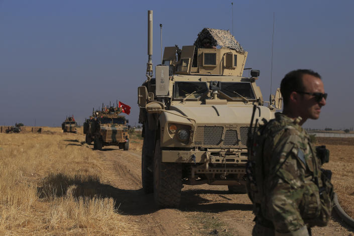 """FILE - This Friday, Oct. 4, 2019 file photo, Turkish and American armored vehicles patrol as they conduct joint ground patrol in the so-called """"safe zone"""" on the Syrian side of the border with Turkey, near the town of Tal Abyad, northeastern Syria. President Donald Trump's announcement that U.S. troops in Syria would step aside to make way for a Turkish military operation against U.S.-allied Syrian Kurdish fighters unleashed a torrent of near unanimous criticism and warnings of immediate and long-term negative consequences. (AP Photo/Baderkhan Ahmad, File)"""
