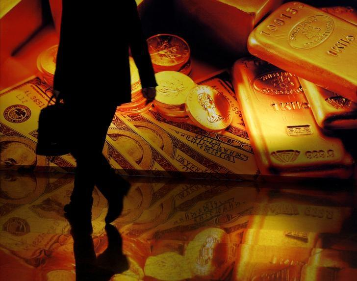 A participant walks past a poster showing gold products at the Asian Financial Forum in Hong Kong