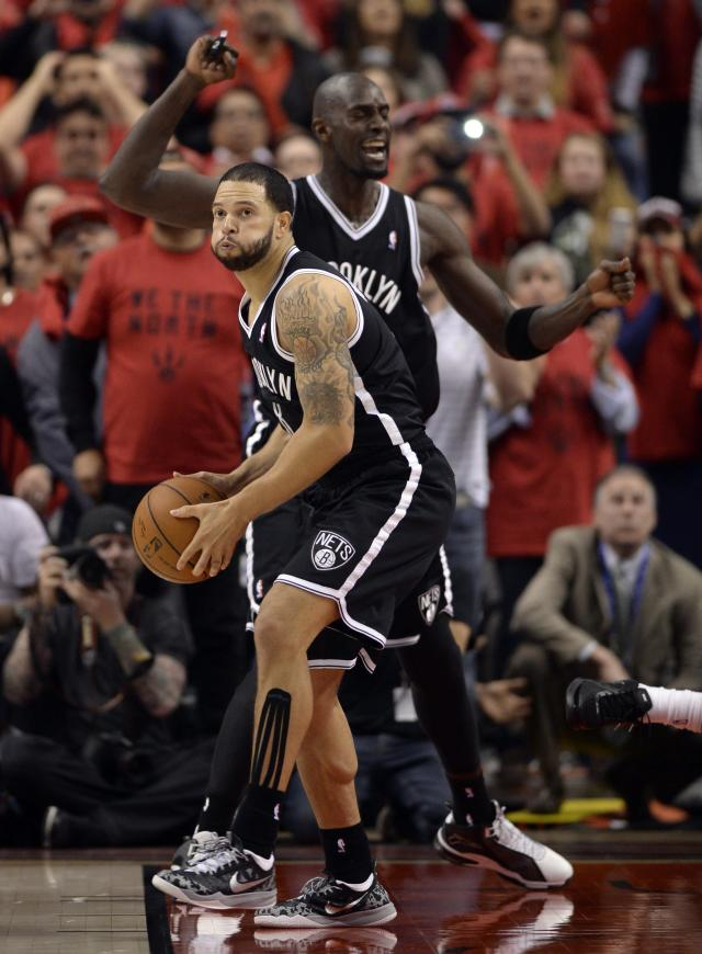 Brooklyn Nets' Deron Williams, front, and Kevin Garnett celebrate after defeating the Toronto Raptors in Game 7 of the opening-round NBA basketball playoff series in Toronto, Sunday, May 4, 2014. (AP Photo/The Canadian Press, Frank Gunn)