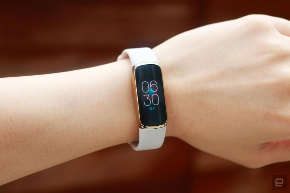 <p>Front view of the Fitbit Luxe with a light pink silicone band on a wrist against a dark brown background. The screen shows the time is 6:30pm.</p>