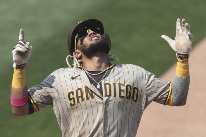 FILE - San Diego Padres' Fernando Tatis Jr. celebrates after hitting a solo home run against the Oakland Athletics during the seventh inning of a baseball game in Oakland, Calif., in this Sunday, Sept. 6, 2020, file photo. The 22-year-old star shortstop signed a $340 million, 14-year deal with the San Diego Padres, the third-highest deal in the sport's history. But the son of the only major leaguer to hit two grand slams in one inning will be giving up a percentage of his fortune to Big League Advance, a company founded in 2016 by former minor league pitcher Michael Schwimer to invest in prospects seeking an appreciation. (AP Photo/Jed Jacobsohn, File)