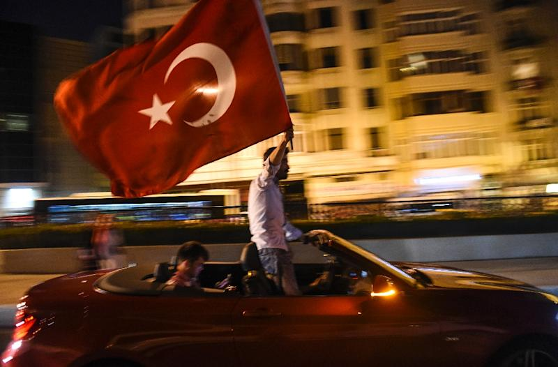 After facing down the bloodiest challenge to his 13-year rule, President Recep Tayyip Erdogan triumphantly addressed flag-waving supporters in Istanbul (AFP Photo/Bulent Kilic)