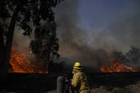 A firefighter watches flames from the Silverado Fire, Monday, Oct. 26, 2020, in Irvine, Calif. A fast-moving wildfire forced evacuation orders for 60,000 people in Southern California on Monday as powerful winds across the state prompted power to be cut to hundreds of thousands to prevent utility equipment from sparking new blazes. (AP Photo/Jae C. Hong)