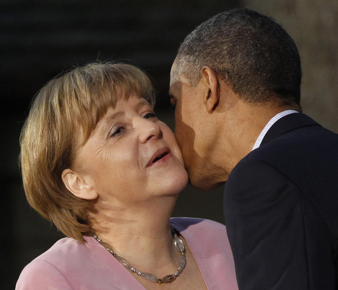 President Barack Obama kisses German Chancellor Angela Merkel on the cheek on arrival for the G8 Summit Friday, May 18, 2012 at Camp David, Md. (AP Photo/Charles Dharapak)
