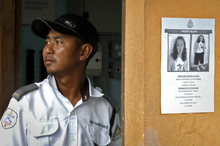 A security guard stands next to a notice showing a missing British girl in Seremban, Malaysia, Sunday, Aug. 11, 2019. The parents of 15-year-old London girl Nora Anne Quoirin who mysteriously disappeared from a Malaysian resort a week ago said Saturday that she wasn't independent and had difficulty walking, in new details to support their conviction that she was abducted. (AP Photo/FL Wong)