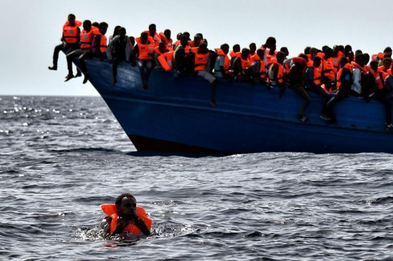Migrants wait to be rescued as they drift in the Mediterranean Sea off the coast of Libya on October 3, 2016
