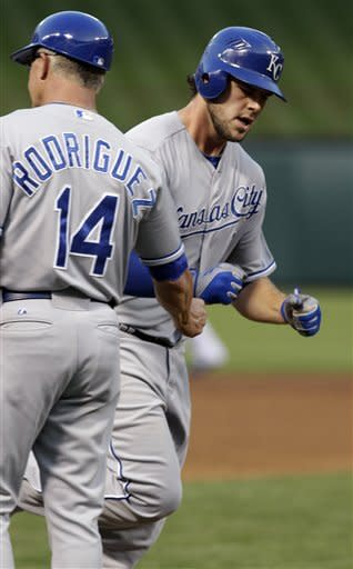 Kansas City Royals' Mike Moustakas, right, celebrates with third base coach Eddie Rodriguez (14) while rounding the bases after hitting a solo home run against the Texas Rangers during the fourth inning of a baseball game, Tuesday, May 15, 2012, in Arlington, Texas. (AP Photo/LM Otero)