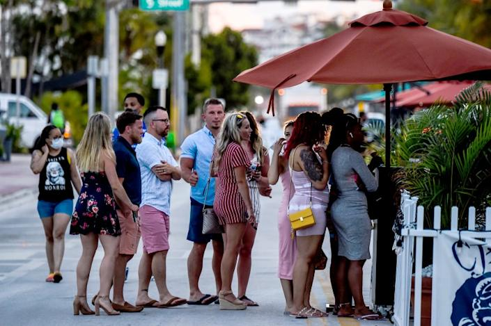 """People in line to enter a restaurant in Miami Beach in late June. Spread on social media, scenes like this can affect the behavior of people in other states with stricter coronavirus orders. <span class=""""copyright"""">(Chandan Khanna / AFP via Getty Images)</span>"""