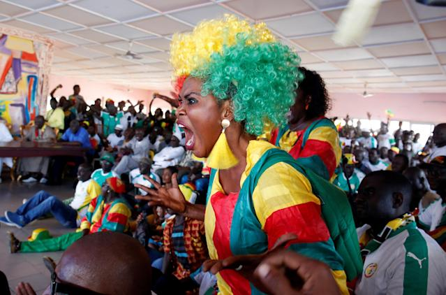 Soccer Football - World Cup - Group H - Japan vs Senegal - Abidjan, Ivory Coast - June 24, 2018. A Senegalese fan reacts as she watches the match on a screen. REUTERS/Luc Gnago