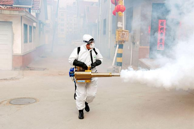 A Chinese volunteer wearing the protective clothing disinfects a street for prevention of coronavirus (Costfoto/Sipa USA)