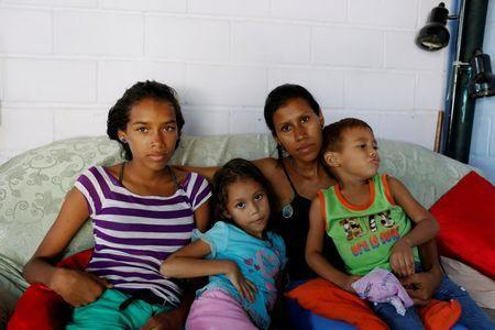 Alejandra Jordan (2nd R), 30, poses for a picture with her children (L-R) Valentina, 13, Valeria, 6, and Josue, 4, ahead of her sterilization surgery, at their home in San Francisco de Yare, Venezuela July 11, 2016. REUTERS/Carlos Garcia Rawlins