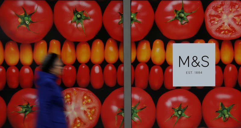 FILE PHOTO: A woman walks past a branch of Marks and Spencer in Altrincham, Britain