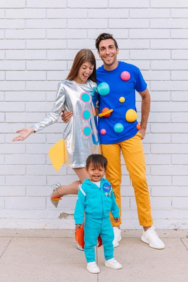 """<p>You don't need a spaceship to bring the wonder of outer space right to your home this year! Instead, opt for a metallic dress, a few bold """"planet"""" shapes, and of course, a tiny NASA outfit for the littlest one in your bunch.</p><p><strong>Get the tutorial at <a href=""""https://studiodiy.com/2018/10/03/diy-space-family-costume/"""" rel=""""nofollow noopener"""" target=""""_blank"""" data-ylk=""""slk:Studio DIY"""" class=""""link rapid-noclick-resp"""">Studio DIY</a>.</strong></p><p><a class=""""link rapid-noclick-resp"""" href=""""https://www.amazon.com/ASMAX-HaoDuoYi-Casual-Sleeve-Silver/dp/B01NBC5T4X?tag=syn-yahoo-20&ascsubtag=%5Bartid%7C10050.g.29074815%5Bsrc%7Cyahoo-us"""" rel=""""nofollow noopener"""" target=""""_blank"""" data-ylk=""""slk:SHOP SILVER DRESSES"""">SHOP SILVER DRESSES</a></p>"""