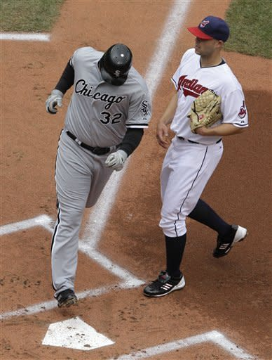 Chicago White Sox's Adam Dunn (32) crosses the plate to score on a wild pitch by Cleveland Indians starting pitcher Justin Masterson, right. in the first inning of a baseball game in Cleveland on Wednesday, April 11, 2012. (AP Photo/Amy Sancetta)