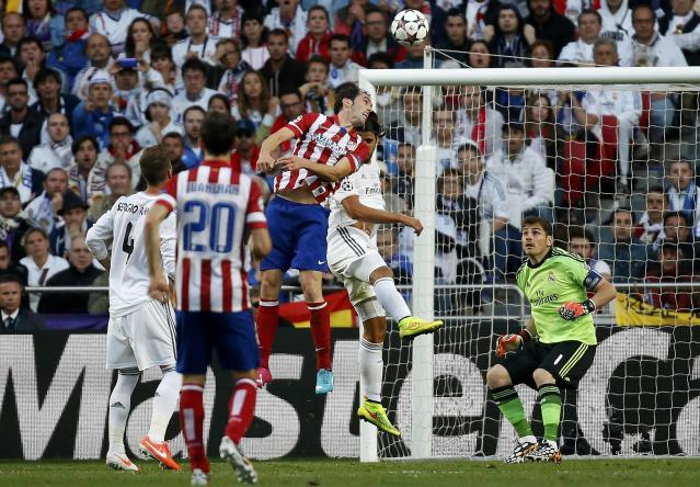 Atletico Madrid's Diego Godin (C) jumps and shoots the first goal for the team during their Champions League final soccer match against Real Madrid at the Luz Stadium in Lisbon May 24, 2014. REUTERS/Paul Hanna (PORTUGAL - Tags: SPORT SOCCER TPX IMAGES OF THE DAY)