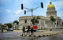 Policemen stand near the Havana Capitol, on July 12, 2021, the day after historic anti-government protests broke out