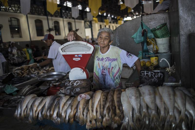 In this Sept. 7, 2019 photo, fish vendor Paulo Pedra works at in the Ver-o-Peso riverside market in Belém, Brazil. The Market brings together 2,000 stalls and traders and is located near to the old Iron market. (AP Photo/Rodrigo Abd)