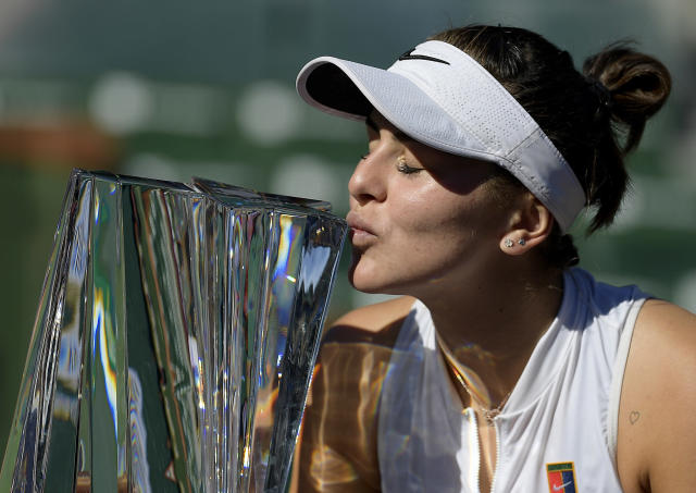 FILE - In this March 17, 2019, file photo, Bianca Andreescu, of Canada, kisses her trophy after defeating Angelique Kerber, of Germany, in the women's final at the BNP Paribas Open tennis tournament in Indian Wells, Calif. Andreescu, 18, is seeded at a Grand Slam tournament for the first time at the 2019 French Open, where play begins Sunday. (AP Photo/Mark J. Terrill, File)