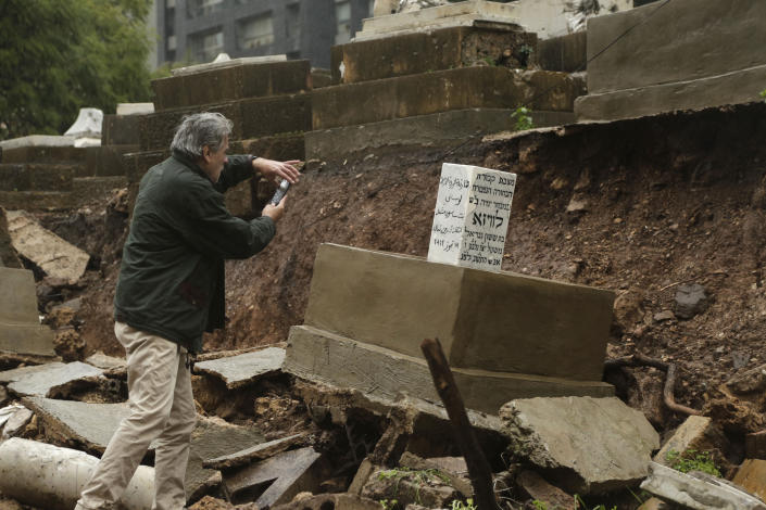 CORRECTS TO CAPITAL'S ONLY JEWISH CEMETERY, NOT COUNTRY'S - A man takes a picture of graves in a Jewish cemetery damaged from heavy rains in the Sodeco area of Beirut, Lebanon, Thursday, Dec. 26, 2019. A heavy storm hit Lebanon with heavy rain and strong winds causing an old wall to collapse in the capital's only Jewish cemetery, causing damage to several tombstones. Lebanon once had a thriving Jewish community, but the various Arab-Israeli wars and Lebanon's own 1975-90 civil war caused waves of emigration and almost none are left in the country today. (AP Photo/Hassan Ammar)