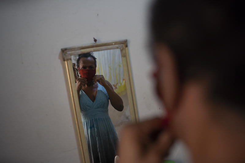 Transgender Claudinha is reflected in a mirror as she puts on a protective face mask inside her room at the squat known as Casa Nem, in Rio de Janeiro, Brazil, Wednesday, July 8, 2020. The six-floor building is home to about 50 LGBTQ people riding out the new coronavirus pandemic behind closed doors. (AP Photo/Silvia Izquierdo)