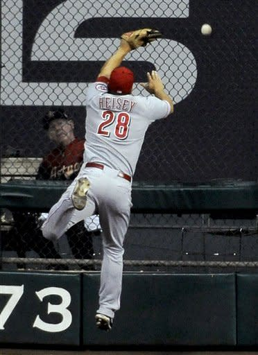 Cincinnati Reds right fielder Chris Heisey cannot make the catch giving Houston Astros' Chris Johnson an RBI double in the fifth inning of a baseball game, Monday, July 23, 2012, in Houston. Astros bullpen assistant Stretch Suba, left, watches. (AP Photo/Pat Sullivan)