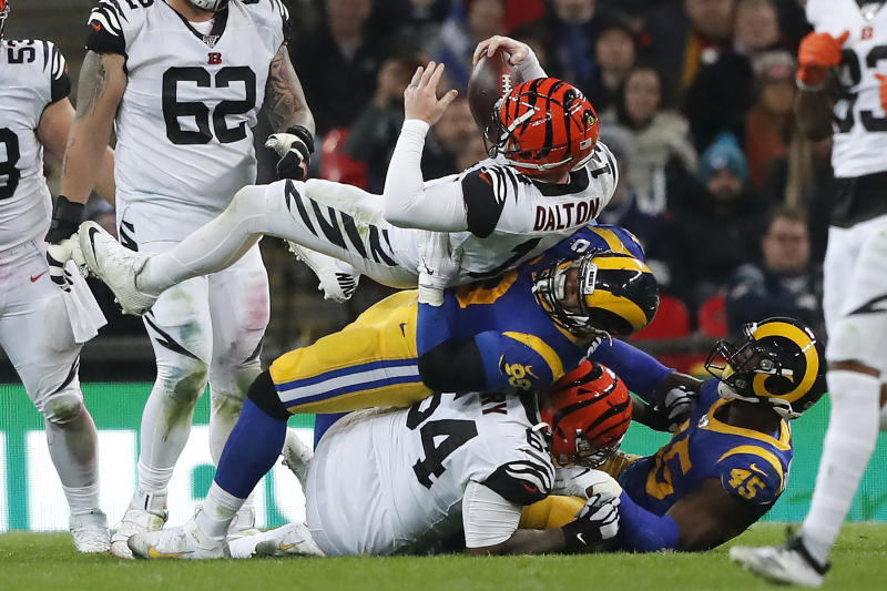 Cincinnati Bengals quarterback Andy Dalton, top, is sacked by Los Angeles Rams defensive tackle Aaron Donald during the second half of an NFL football game, Sunday, Oct. 27, 2019, at Wembley Stadium in London. (AP Photo/Frank Augstein)