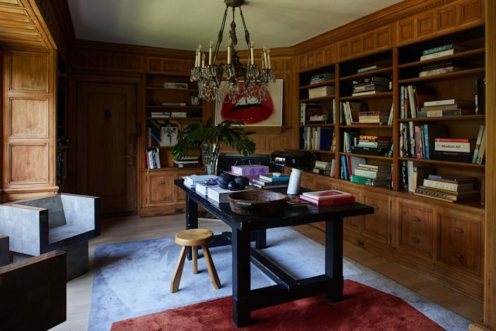 "<div class=""caption""> In the library, an <a href=""https://www.restorationhardware.com/"" rel=""nofollow noopener"" target=""_blank"" data-ylk=""slk:RH"" class=""link rapid-noclick-resp"">RH</a> desk and Charlotte Perriand stool sit atop a <a href=""https://christopherfarr.com/"" rel=""nofollow noopener"" target=""_blank"" data-ylk=""slk:Christopher Farr"" class=""link rapid-noclick-resp"">Christopher Farr</a> rug. A vintage chandelier hangs overhead. Dahan hand-sanded wood walls to give them a natural, unfinished look. </div>"