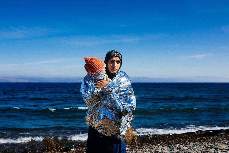 A woman holds her child wrapped in an emergency blanket shortly after arriving with other migrants on the Greek island of Lesbos on October 15, 2015