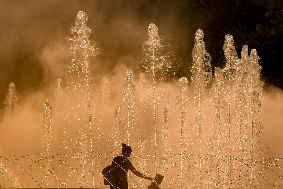 A woman holds a little girl's hand as she walks by city fountains at sunset, at the end of a very warm day, in Bucharest, Romania, Friday, July 9, 2021. The Romanian weather authority has issued a heatwave warning for the next two days in the Romanian capital with temperatures expected to go above 33 degrees centigrade (91.4 Fahrenheit) in the shade. (AP Photo/Andreea Alexandru)