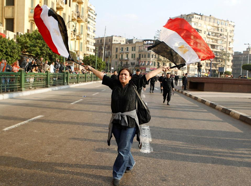 An anti-government protester waves Egyptian flags during clashes with police in downtown Cairo on 25 January 2011.REUTERS