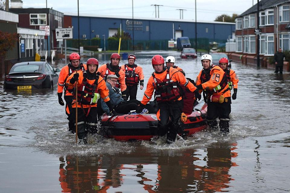Members of the Fire and Rescue service evacuate an elderly resident to dry land in Doncaster (AFP via Getty Images)
