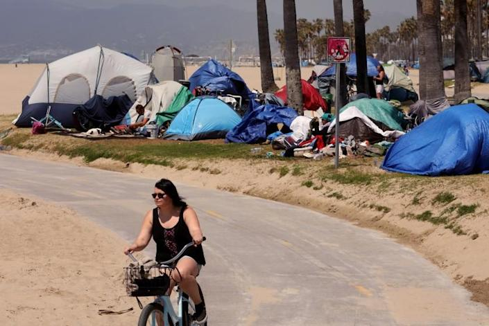 VENICE, CA - APRIL 16, 2021 - - A bicyclists rides past several homeless tents along the bike path in Venice on April 16, 2021. (Genaro Molina / Los Angeles Times)