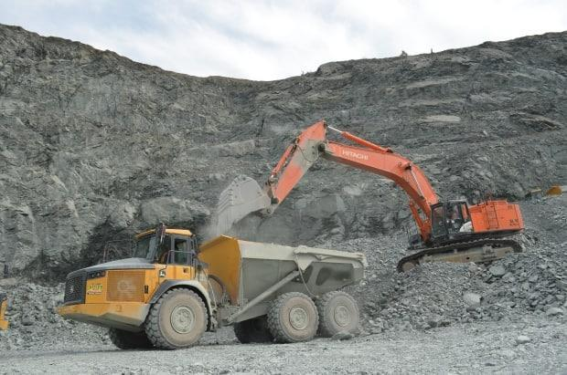 An excavator fills a dump truck with crushed rock in Anaconda's open-pit mine in Newfoundland. (Zach Goudie/CBC - image credit)
