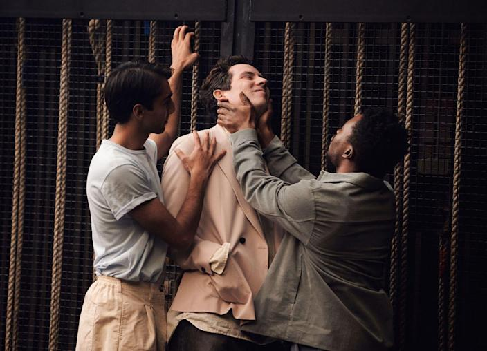 Two young Black men grab and hold a white man.