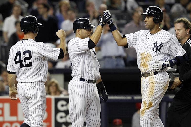 New York Yankees' Brett Gardner, left, and Russell Martin, center, greet Derek Jeter at the plate after Jeter's fourth-inning, three-run home run against the Los Angeles Angels during their baseball game at Yankee Stadium in New York, Sunday, April 15, 2012. (AP Photo/Kathy Willens)