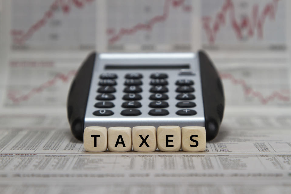 The word taxes spelled out in tiles in front of a calculator, sitting on papers with lists on them and stock charts in the background.
