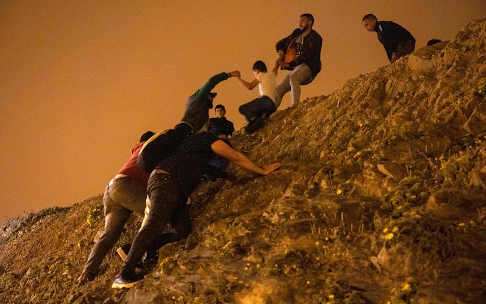Moroccan migrants climb rocks on the shoreline in the northern town of Fnideq, with a policeman watching from the top of the slope - FADEL SENNA/AFP via Getty Images