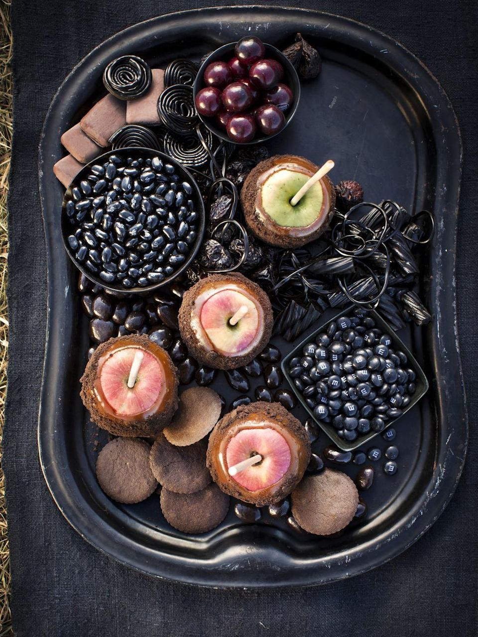 """<p>Equal parts sweet and spooky, this eerie platter is such a festive way to serve your favorite treats. To create a similar spread, fill a board or tray with black licorice, jelly beans, M&M's, chocolate cookies, chocolate-covered nuts, and dried fruit. Add Ree's <a href=""""https://www.thepioneerwoman.com/food-cooking/recipes/a34029134/cookie-coated-caramel-apples-recipe/"""" rel=""""nofollow noopener"""" target=""""_blank"""" data-ylk=""""slk:cookie-coated caramel apples"""" class=""""link rapid-noclick-resp"""">cookie-coated caramel apples</a> to finish it off.</p><p><a class=""""link rapid-noclick-resp"""" href=""""https://go.redirectingat.com?id=74968X1596630&url=https%3A%2F%2Fwww.walmart.com%2Fsearch%2F%3Fquery%3Dthe%2Bpioneer%2Bwoman%2Bserving%2Bplatters&sref=https%3A%2F%2Fwww.thepioneerwoman.com%2Ffood-cooking%2Fmeals-menus%2Fg32110899%2Fbest-halloween-desserts%2F"""" rel=""""nofollow noopener"""" target=""""_blank"""" data-ylk=""""slk:SHOP SERVING PLATTERS"""">SHOP SERVING PLATTERS</a></p>"""