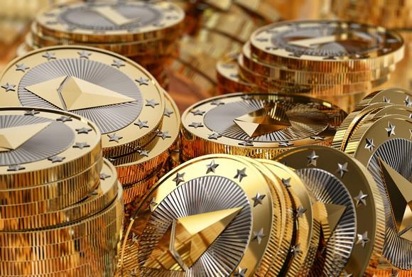 Messy piles of physical silver and gold Ethereum coins.