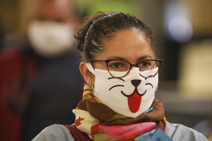 A woman wearing a face mask decorated with an animal face waits in line for a rapid coronavirus test at a train station in Buenos Aires, Argentina, Friday, April 24, 2020. (AP Photo/Natacha Pisarenko)