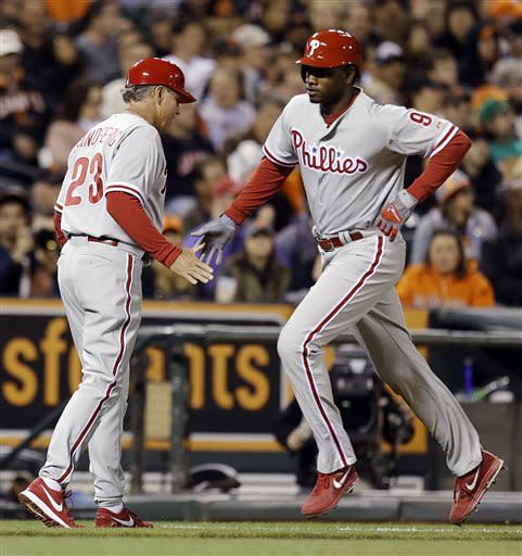 Philadelphia Phillies' Domonic Brown, right, is congratulated by third base coach Ryne Sandberg after hitting a home run off San Francisco Giants' Madison Bumgarner in the fifth inning of a baseball game, Monday, May 6, 2013, in San Francisco. (AP Photo/Ben Margot)