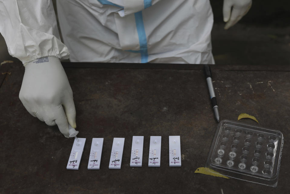 A health worker conducts rapid antigen test for COVID-19 in New Delhi, India, Tuesday, Sept. 1, 2020. India has now reported more than 75,000 infections for five straight days, one of the highest in the world, just as the government began easing restrictions to help the battered economy. (AP Photo/Manish Swarup)