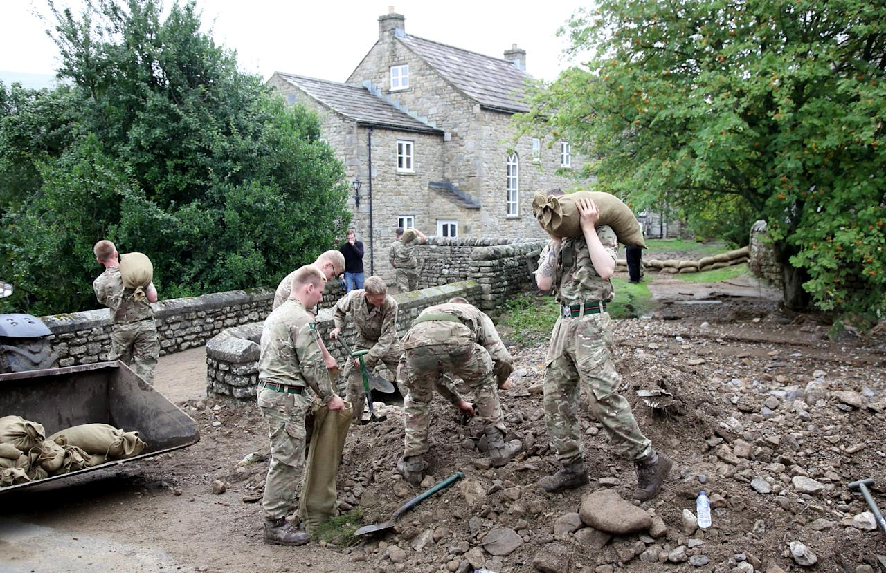 Soldiers help local residents following flash flooding in Grinton, North Yorkshire (Picture: SWNS)